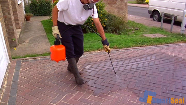 Sealant being sprayed onto the surface of the paving